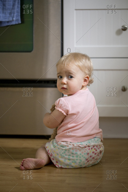 Cute baby girl sitting on kitchen floor
