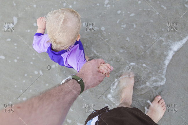 Overhead view of father holding baby girl's hand while walking on beach