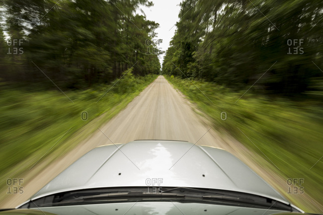 Vehicle speeding down an off-road trail in forest