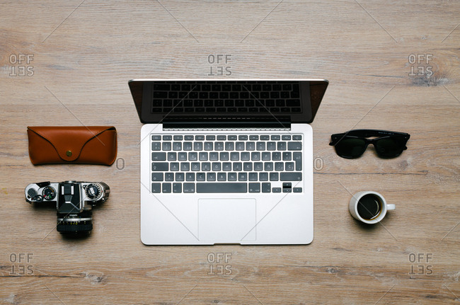 Overhead view of wooden desk with objects and miniature cup of coffee