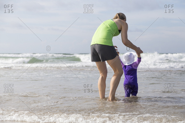 Mother holding toddler's hands as she explores the beach