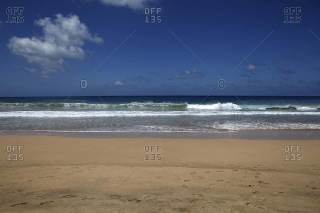 Waves by beach under blue sky