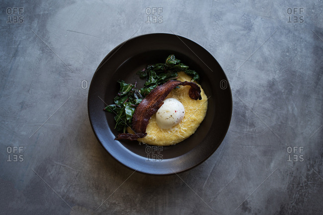 Breakfast dish with bacon, wilted greens, hard boiled egg, and polenta