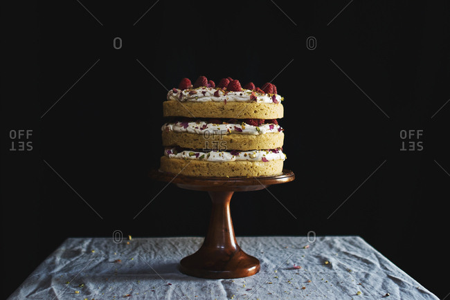 Layered cake with icing and raspberries served on cake stand