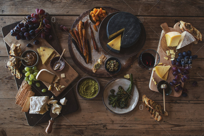 A variety of cheeses, breads, fruits, and vegetables on serving boards and platters