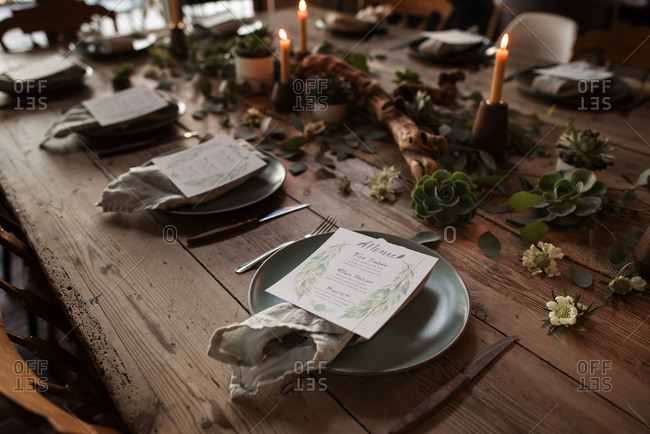Place settings on wooden table with menus and cloth napkins on plates