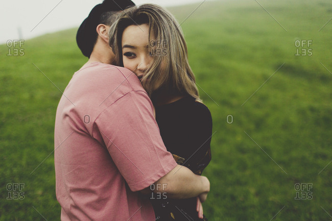 Woman looking over her fiance's shoulder as they embrace