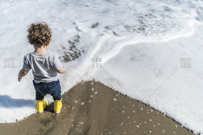 Toddler in boots by the sea