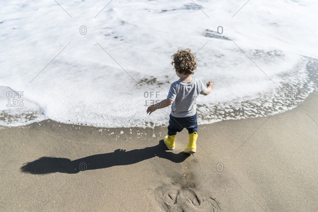 Toddler in boots walking on beach