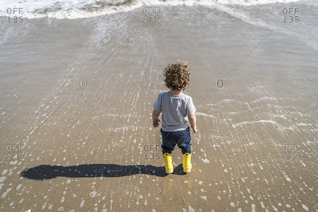 Toddler on beach making a shadow