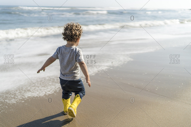 Toddler in boots walking along beach