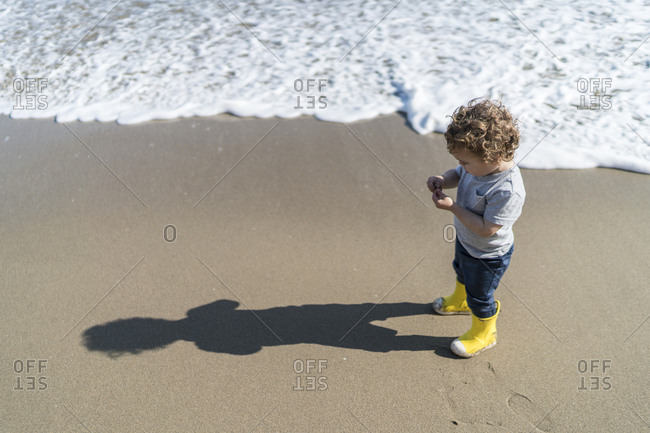 Toddler on beach making long shadow