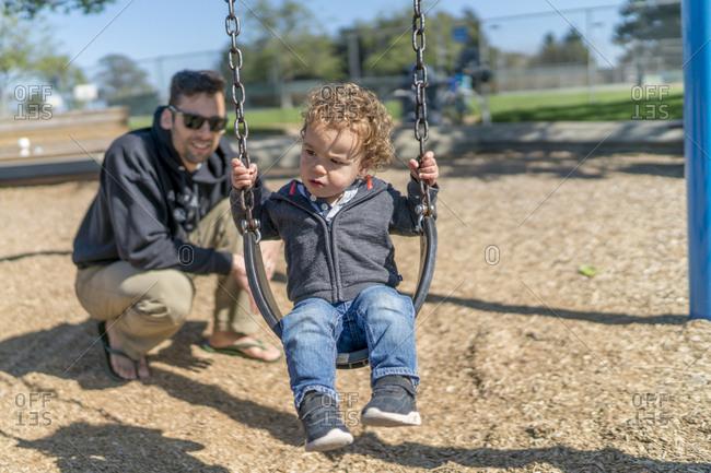 Dad pushing toddler boy on swing