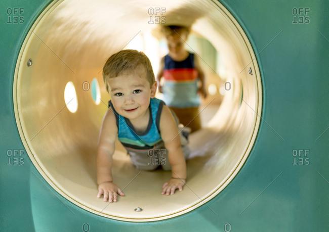 Little boys in playground tunnel