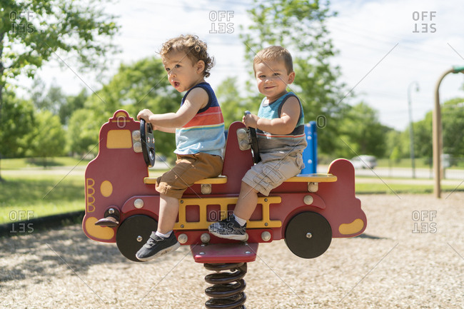 Boys on spring ride toy in park
