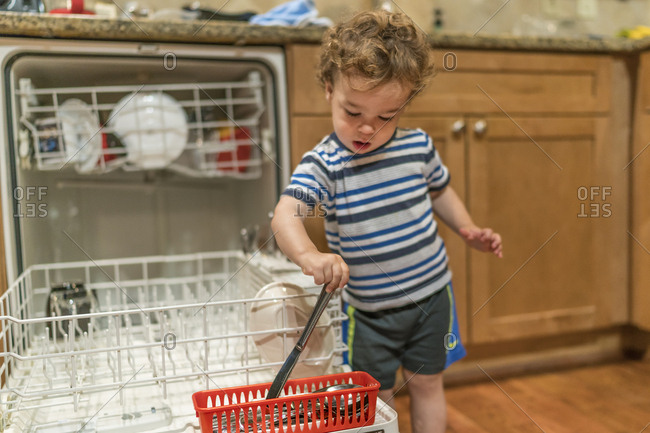 Toddler boy helping load dishwasher