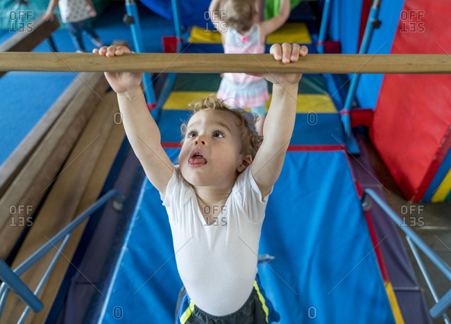 Boy hanging from bar in children's gym