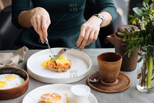 Woman eating salmon eggs benedict