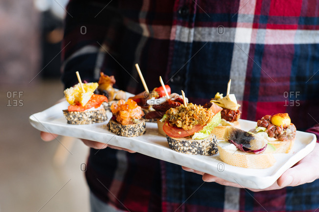Man holding seafood appetizer tray