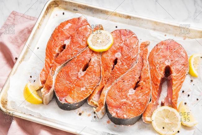 Raw salmon slices on baking pan