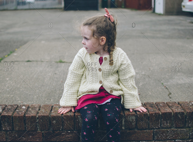 Girl in cardigan sitting by driveway