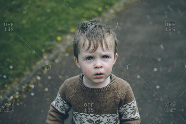 Boy in knit sweater standing outside