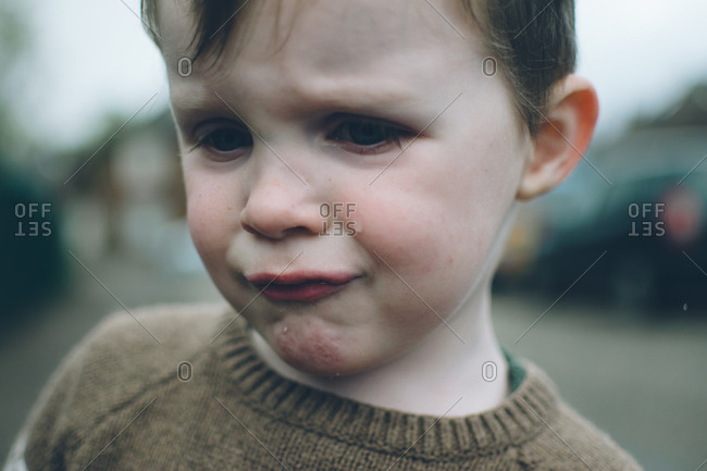 A crying boy in sweater outside