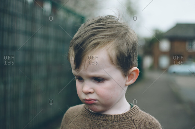 A little boy crying in street