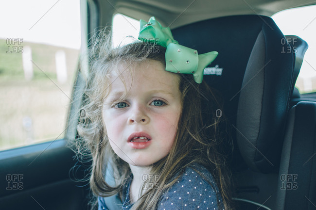 Girl with hair bow riding in car