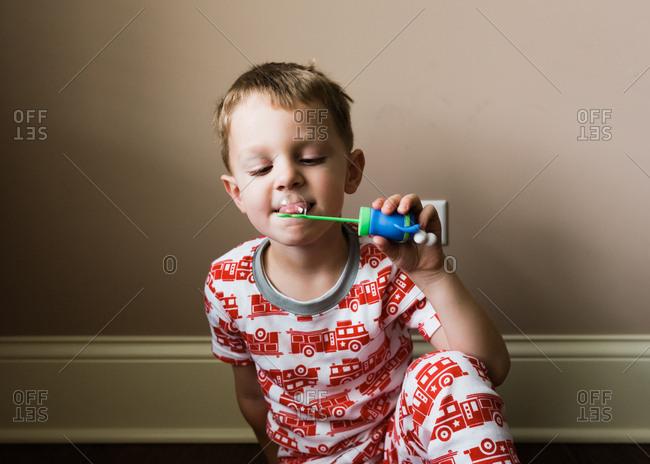 Boy licking bubble on wand
