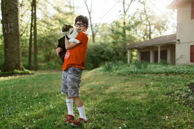 Boy in front yard holding a cat