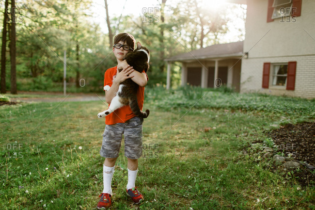 Boy in front yard holding cat