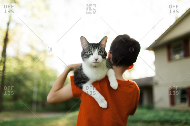Cat on a boy's shoulder in yard