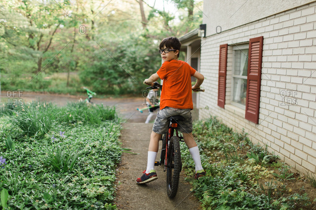 Boy riding bike on path in yard
