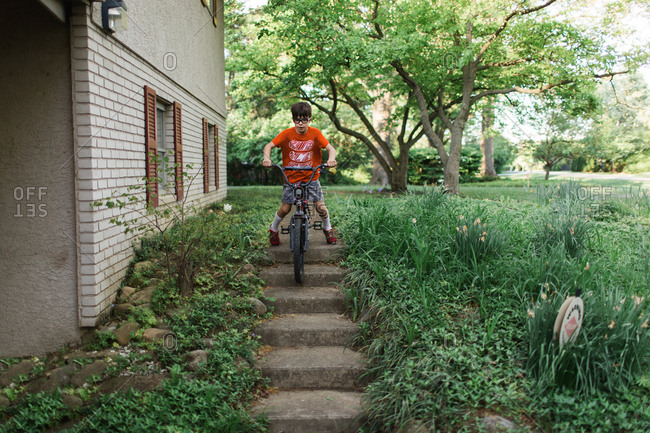 Boy riding bike down stairs in yard