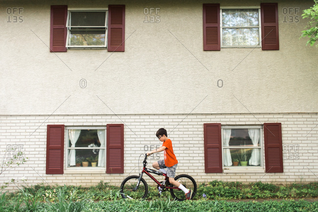 Boy riding bike alongside house