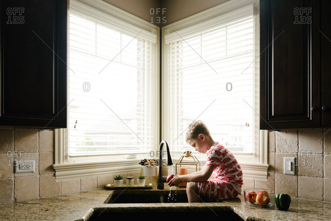 Boy rinsing apple in faucet
