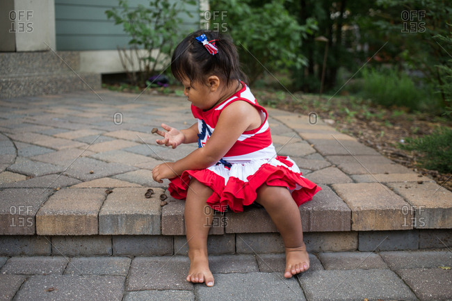 Little girl wearing a red, white, and blue dress playing with acorn caps while sitting on step