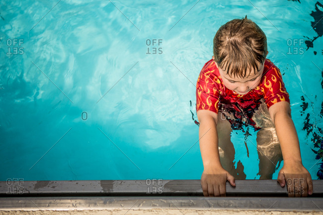 Boy holding on to the edge of a swimming pool