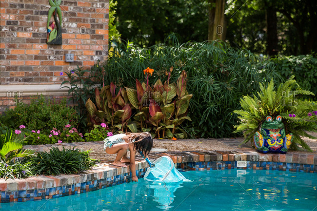 Girl reaching into the water of swimming pool