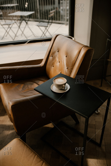 Freshly made latte on side table next to leather chair