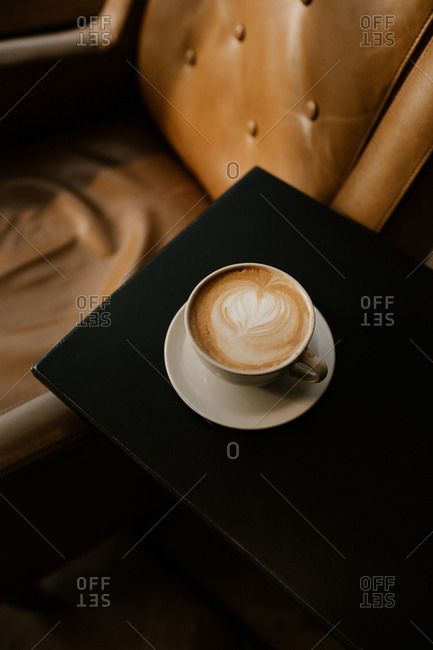 Freshly made latte served on small table next to leather chair