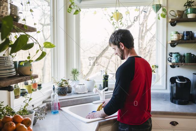 Man washing dishes at kitchen sink