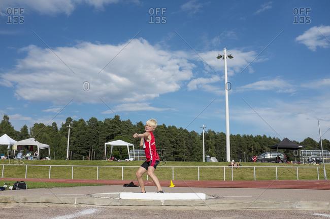 Boy throwing ball at sports facility