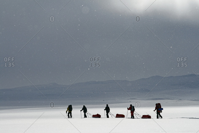 Tourists cross country skiing against mountain scenery