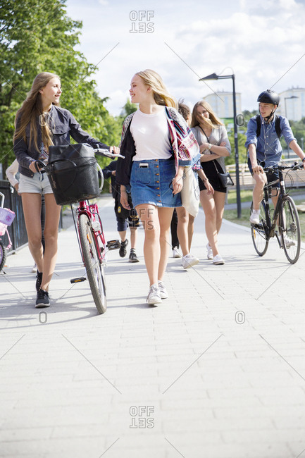 Teenagers with bicycles walking in city