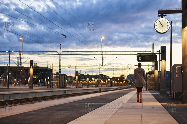Woman in workout clothes walking away at train station