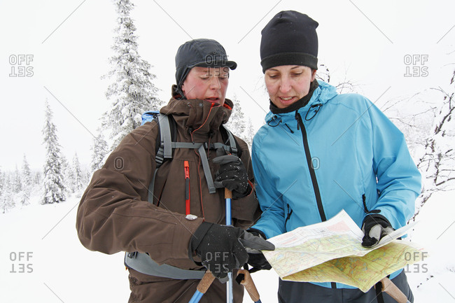 Women looking at map in winter forest