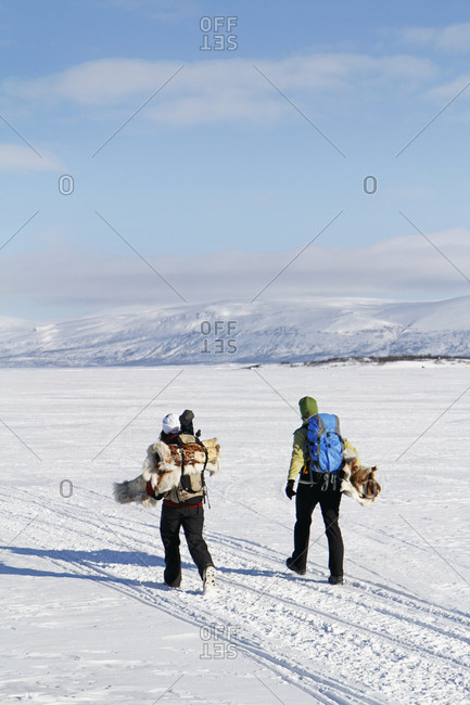 People carrying ice fishing equipment