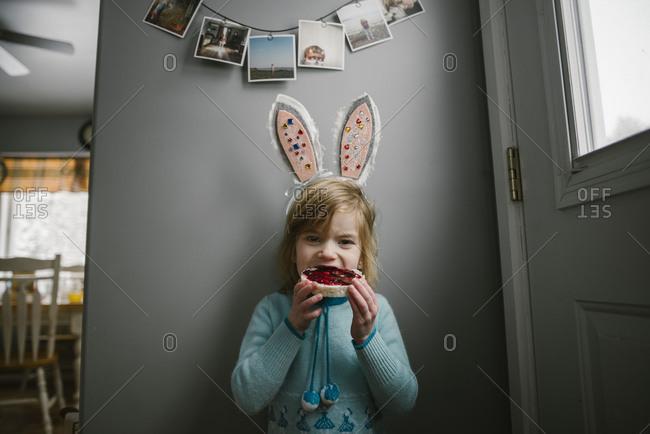 Girl in Easter ears eating tart